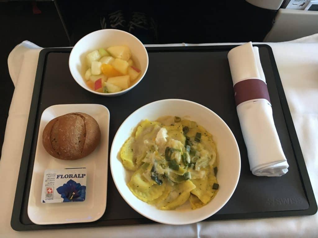 Taleggio-Kräuter-Cappelletti mit Weißweinsauce sowie ein Lauch-Wirz-Ragout, begleitet von einem Fruchtsalat